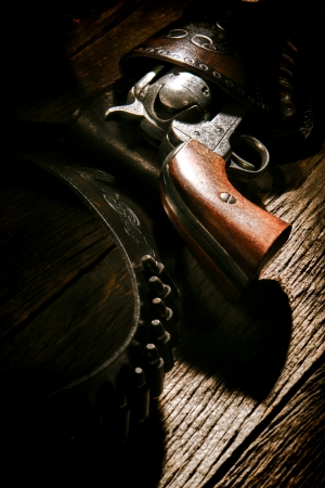 American West legend antique six-shooter revolver gun in vintage cowboy leather holster with old lead bullets on weathered wood plank western saloon table