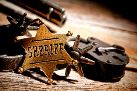 American West legend sheriff star badge lawman medallion with tools of the trade vintage western spurs and antique jail lock with old keys on an ancient wood jailhouse table Imagens - 24987687