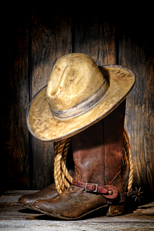 American West rodeo cowboy dirty and used white felt hat atop worn and muddy leather working rancher boots photo