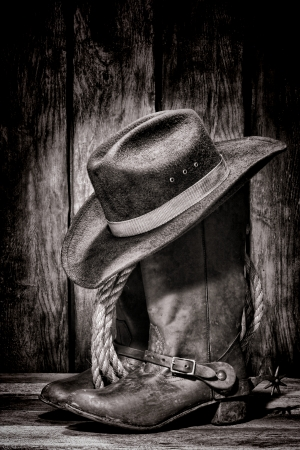 American West rodeo cowboy dirty and used black felt hat atop worn and old leather working rancher boots with vintage spurs and ranching rope in an antique ranch barn photo