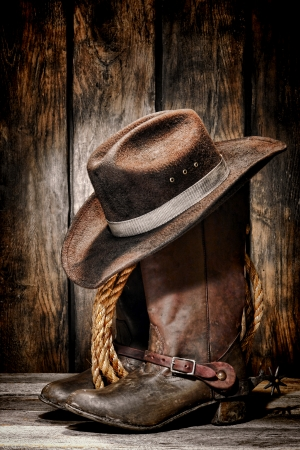 rodeo cowboy dirty and used black felt hat atop worn and old leather working rancher boots Banque d'images