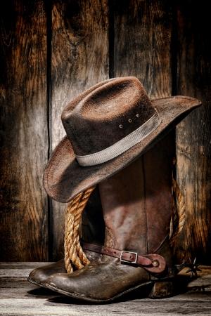 rodeo americano: vaquero de rodeo negro sucio y usado sombrero de fieltro encima de cuero gastado y viejo trabajo botas ranchero Foto de archivo