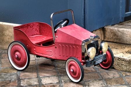 Vintage reproductie 1938 Franse pedaal speelgoedauto met vervaagde rode verf Stockfoto