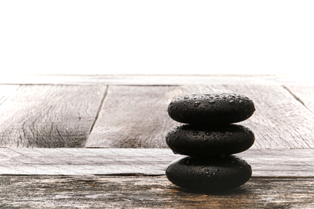 Wet polished smooth hot massage black stones with water drops and droplets in a Zen style cairn on a vintage wood board table in a relaxing wellness holistic spa for relaxation and health rejuvenation treatment