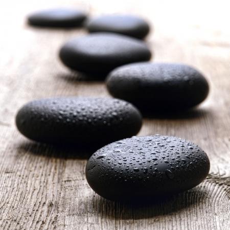 ホット マッサージ黒い石を洗練された滑らかなウェット水滴とリラクゼーションと健康若返り治療のためのリラックスしたウェルネスのホリスティックスパでヴィンテージの木製ボード テーブル上のパスをなだめるような禅スタイルの滴で覆われて 写真素材 - 25295252