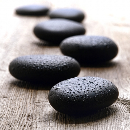 Wet smooth polished hot massage black stones covered with water drops and droplets in a Zen style soothing path on a vintage wood board table in a relaxing wellness holistic spa for a relaxation and good health rejuvenation treatment Stok Fotoğraf