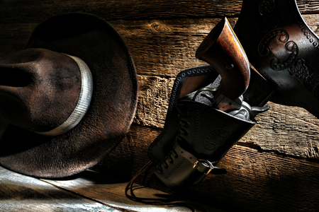 holster: American West Legend cowboy vintage revolver gun in antique leather holster hanging on a ranch wood wall with worn brown felt western hat