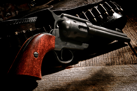 American West legend antique six-shooter revolver gun and vintage cowboy leather bullet belt with pistol holster on weathered wood board western ranch table Banque d'images