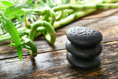 Wet black smooth polished hot massage stones drenched with water drops and droplets in a Zen style  Imagens