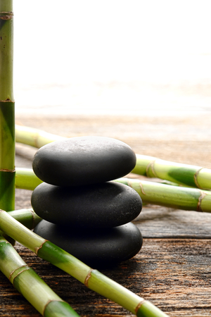 Black smooth polished hot massage stones stack in a Zen style cairn with bamboo shoots on an old weathered wood plank table in a relaxing wellness holistic spa before a rejuvenation and relaxation health session