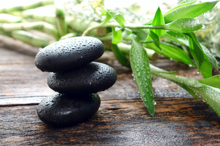 Wet black smooth polished hot massage stones drenched with water drops photo