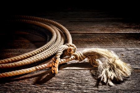 hondo: American West rodeo authentic cowboy lariat lasso with hondo or honda noose loop rawhide speed burner and end tassel on vintage weathered western barn wood planks