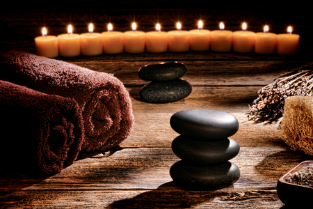 cairn: Black polished smooth hot massage stones in a Zen inspired cairn on a vintage wood boards table in a rustic natural and holistic spa for a traditional relaxation and health rejuvenation treatment
