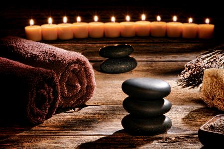 Zwart glad gepolijst hot massage stenen in een Zen geïnspireerd steenhoop op een vintage houten planken tafel in een rustieke natuurlijke en holistische spa voor een traditionele ontspanning en gezondheid verjongingskuur Stockfoto