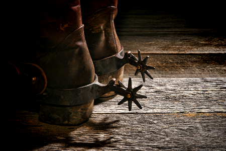 legends folklore: American West rodeo vintage Western riding spurs on traditional leather cowboy boots with dirty worn heels on old weathered wood planks in a western ranch Stock Photo