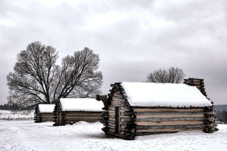 American Revolutionary War soldier housing wood log cabins in an encampment in winter snow at Valley Forge National Historical Park military camp of the Continental Army near Philadelphia in Pennsylvania photo