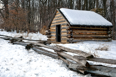 American Revolutionary War soldier housing wood cabin with wooden fence in an encampment in winter snow at Valley Forge National Historical Park military camp of the Continental Army near Philadelphia in Pennsylvania photo