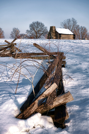 Split rail fencing enclosure fence and American Revolutionary War soldier housing wood cabin in an encampment in winter snow at Valley Forge National Historical Park military camp of the Continental Army near Philadelphia in Pennsylvania photo