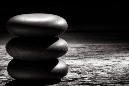 Polished smooth black hot massage stones in a Zen inspired soothing and symbolic cairn on a weathered vintage wood boards table in a relaxing wellness holistic spa for quiet relaxation and health rejuvenation treatment with meditation and well being aware