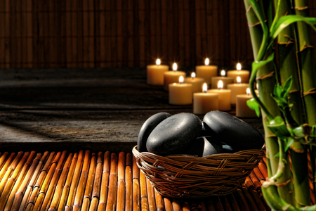 Smooth polished black hot massage stones in a basket with candles burning and bamboo stems decor in the relaxing Zen inspired soothing atmosphere of a wellness holistic spa for a natural well-being rejuvenation session  Stok Fotoğraf