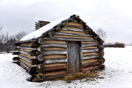 forge: American Revolutionary War humble soldier shelter housing log wood cabin in winter snow at Valley Forge National Historical Park military camp of the Continental Army near Philadelphia in Pennsylvania