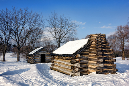forge: American Revolutionary War soldier housing log wood cabins in an encampment in winter snow at Valley Forge National Historical Park military camp of the Continental Army near Philadelphia in Pennsylvania