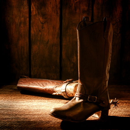 ranching: American West rodeo pair of traditional leather western rodeo cowboy boots with authentic ranching spurs on wooden floor in an old ranch wood barn