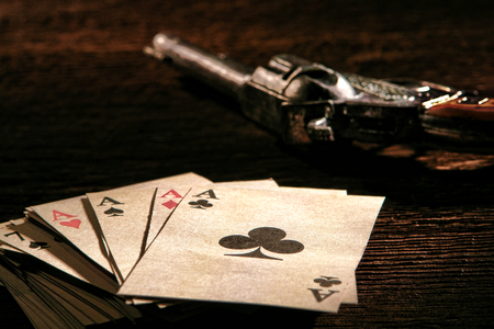 cheater: American West Legend poker game stack of cards with four aces on top and gambler revolver gun on a wood table in an old western gambling saloon scene on the old frontier