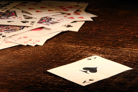 establishment: American West Legend vintage ace of spade playing card and stack of antique poker game cards on a weathered wood table in an old western frontier gambling establishment saloon