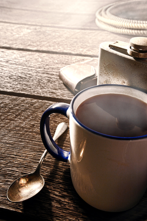 steamy: American West rodeo steamy cup of hot black coffee with steam and vintage alcohol drinking flask with rodeo cowboy gear on an old wood table in the morning at a working western ranch