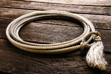 hondo: American West rodeo genuine cowboy lariat lasso with honda noose loop over rawhide speed burner and end tassel on vintage weathered barn wood planks in a western ranch Stock Photo