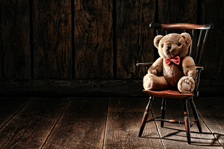 attic: Vintage soft and fluffy teddy bear stuffed animal toy sitting on an old miniature Windsor style armchair in an antique house attic with wood plank floor and aged wooden board walls  Stock Photo