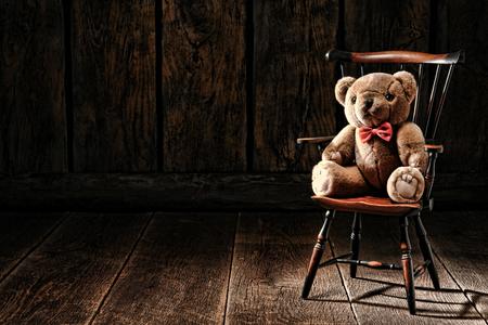 Vintage zacht en pluizige teddybeer gevulde dieren speel goed zitten op een oude miniatuur Windsor stijl fauteuil in een antiek huis zolder met houten plankenvloer en verouderde houten plank muren