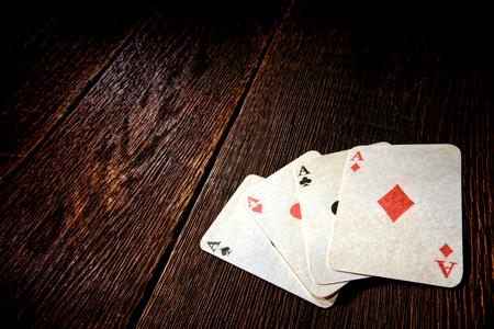 Cuatro ases del juego del póker tarjetas que juegan de la vendimia en una mesa de madera desgastada en un antiguo juego frontera occidental establecimiento saloon Foto de archivo