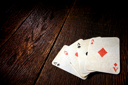 games of chance: Four aces vintage poker game playing cards on a weathered wood table in an old western frontier gambling establishment saloon