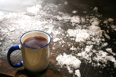coffee table: Hot cup of steamy black coffee with warm comfort steam cloud in a vintage enamel mug with fresh snow on an antique weathered wood table in winter