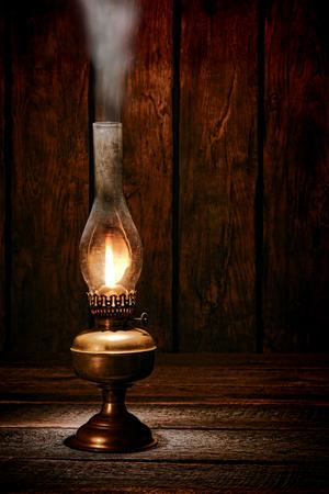 Antieke rustieke kerosine olie lantaarn lamp brandende licht met een zachte gloed vlam waardoor rook op een vintage houten tafel in een oude western ranch schuur