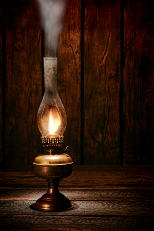 Antique rustic kerosene oil lantern lamp burning light with a soft glow flame making smoke on a vintage wood table in an old western ranch barn  photo
