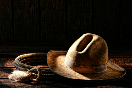 American West rodeo cowboy worn and dirty white felt hat with authentic roping lariat lasso old weathered wood planks in an old western ranch wooden barn in morning light