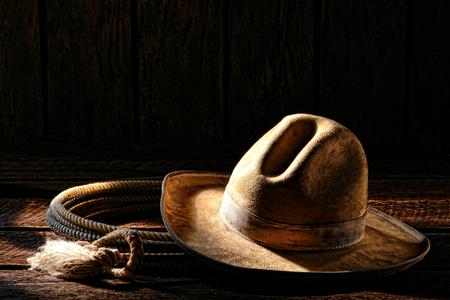 rodeo americano: Vaquero de rodeo del oeste americano gastado y sucio blanco sombrero de fieltro con auténtico lariat cuerda de lazo viejos tablones de madera resistidos en un antiguo granero de madera rancho occidental en luz de la mañana