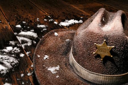 American West Legend natte en versleten vintage lawman cowboyhoed met rechtshandhaving sheriff-ster badge op een antieke houten plank tafel met verse winter sneeuw na een rechtshandhaving koude patrouille plicht aan de westelijke grens