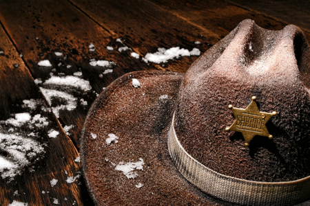 American West Legend wet and worn vintage lawman cowboy hat with law enforcement sheriff star badge on an antique wood plank table with fresh winter snow after a law enforcement cold patrol duty on the western frontier