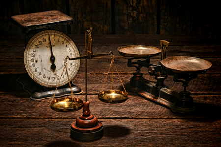 Balance and spring type weight measuring antique and vintage scales with weighing trays on an old weathered shop wood counter