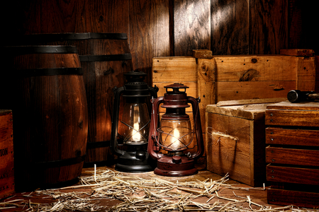 stockroom: Old fashioned light kerosene lantern style oil lamps burning in an antique shipping warehouse stockroom with vintage wooden crates containers and ancient wood storage boxes near retro whisky transportation barrels