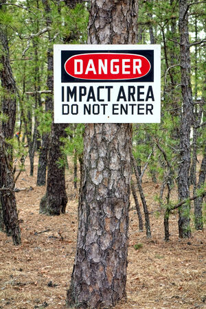 to ensure: Danger impact area do not enter warning sign post on a pine tree at a military installation shooting and firing training range on an army base to prevent unauthorized trespassing and ensure safety by entry prohibition of a dangerous restricted area zone