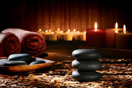 Hot massage black polished stones Zen style cairn and treatment stone tray with soft towels and glowing aromatherapy candles with scattered dry flower petals on old wood planks in a relaxation and wellness holistic spa Banque d'images