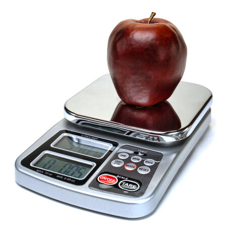 precise: Healthy red apple fruit on a precision kitchen balance scale to measure weight and for precise calories counting for a healthy diet and a nutritious snack food serving