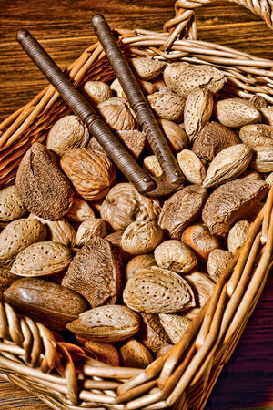 Assortment of nuts in a wicker basket with almonds and walnuts and hazelnuts and chestnuts and pecans and nutmegs with an antique nutcracker  photo