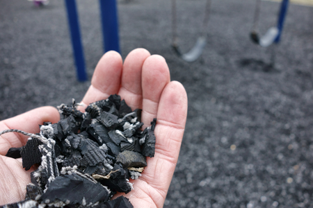 rubber: Shredded and cut pieces of used recycled automobile rubber tire crumb reused as soft surface ground floor filler mulch compound on children amusement playground for safety and injury prevention