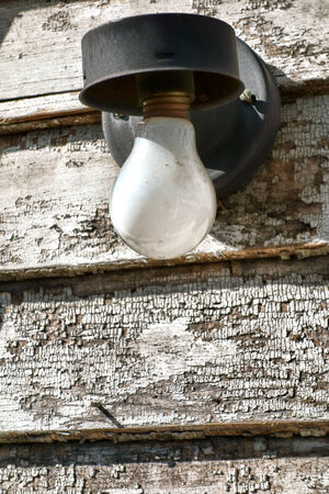outdoor lighting: Frosted incandescent electric light bulb on vintage outdoor electrical lighting fixture on an abandoned house with aged peeling paint on weathered wood clapboard Stock Photo